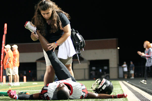 Senior Adriana Jaimes stretches junior Jared Hopper before the varsity football game against Aledo.