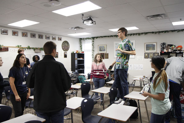 CX Debate Captain senior Ben Schnuck stands on a chair to explain a debate game to the team. Debate has bonded through their shared interest in arguing and logic.