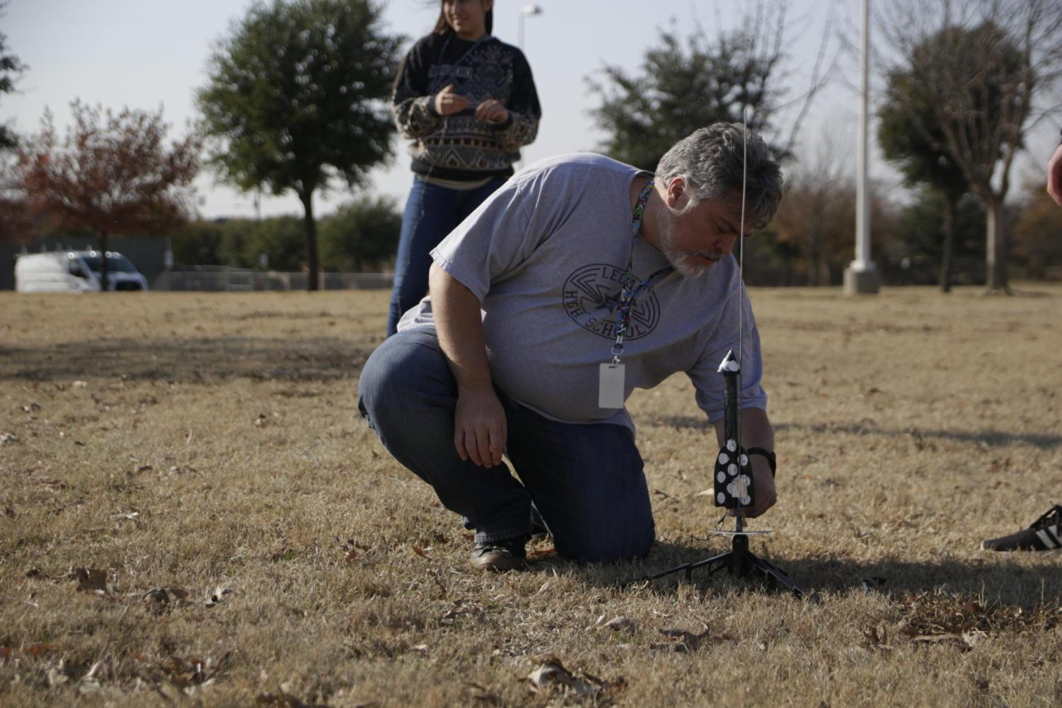 Mr. John Davis sets up a rocket to prepare a group of students for their launch.