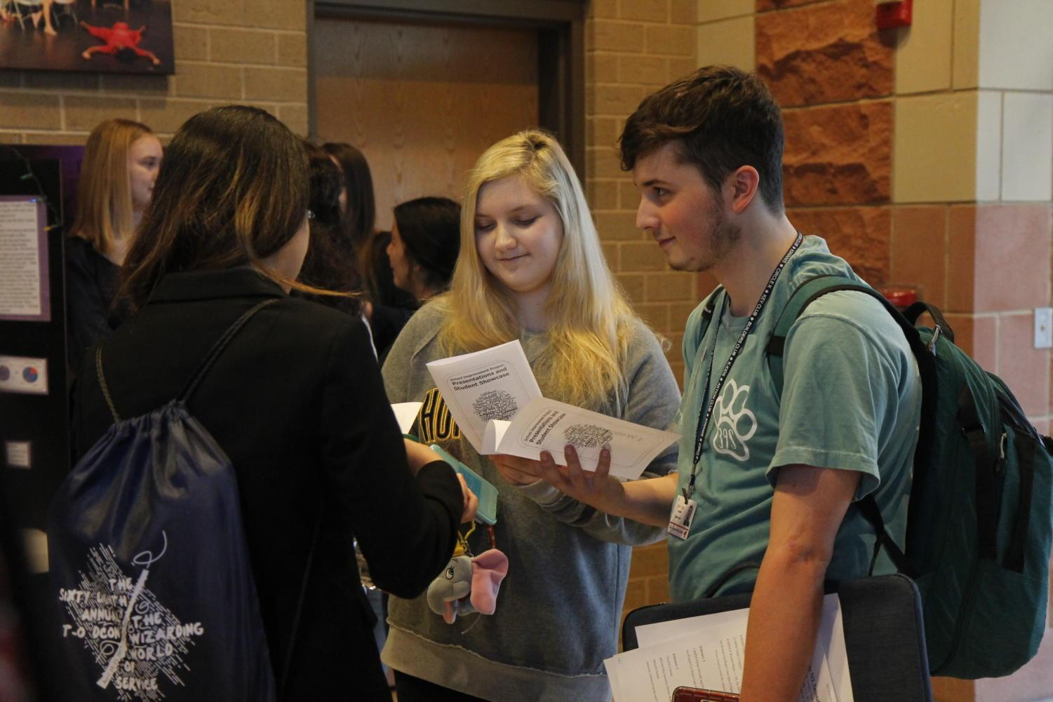 Senior Joseph Castronovo and sophomore Kaitlyn Pasierb discuss the AP English III presentations after the event.