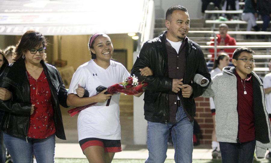 Senior+Dezirae+Rodriguez+walks+the+field+with+her+family+on+Senior+Night.