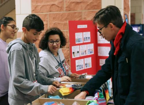 Josh Ipock, 9, sells a pack of socks to Phillip Ipock, 12, during B lunch. Key Club will sell socks for $4 each or $12 for a pack of three during all lunches through Oct. 25 to support Socks for Legs. (Kassidy Duncan photo)