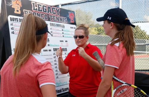 Coach Lisa Osborn instructs Abby Carpenter, 10, and Tatum Sikes, 9, after their doubles match against Granbury players. Varsity tennis will play against Timberview at their next match on Sept. 25. (Cooper Certain photo)