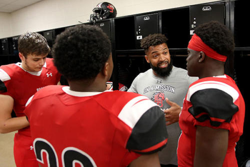 Coach Nolan Crowdus discusses plays with players while on lightning delay against Highland Park on Oct. 12. Legacy lost to the Scots 28-7. (Zane Hudson photo)