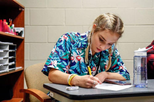 Elizabeth Fox, 12, works on homework in between running passes during office aid. Students in office aid deliver passes and help assist the office with any other errands. (Grant Gourley photo)